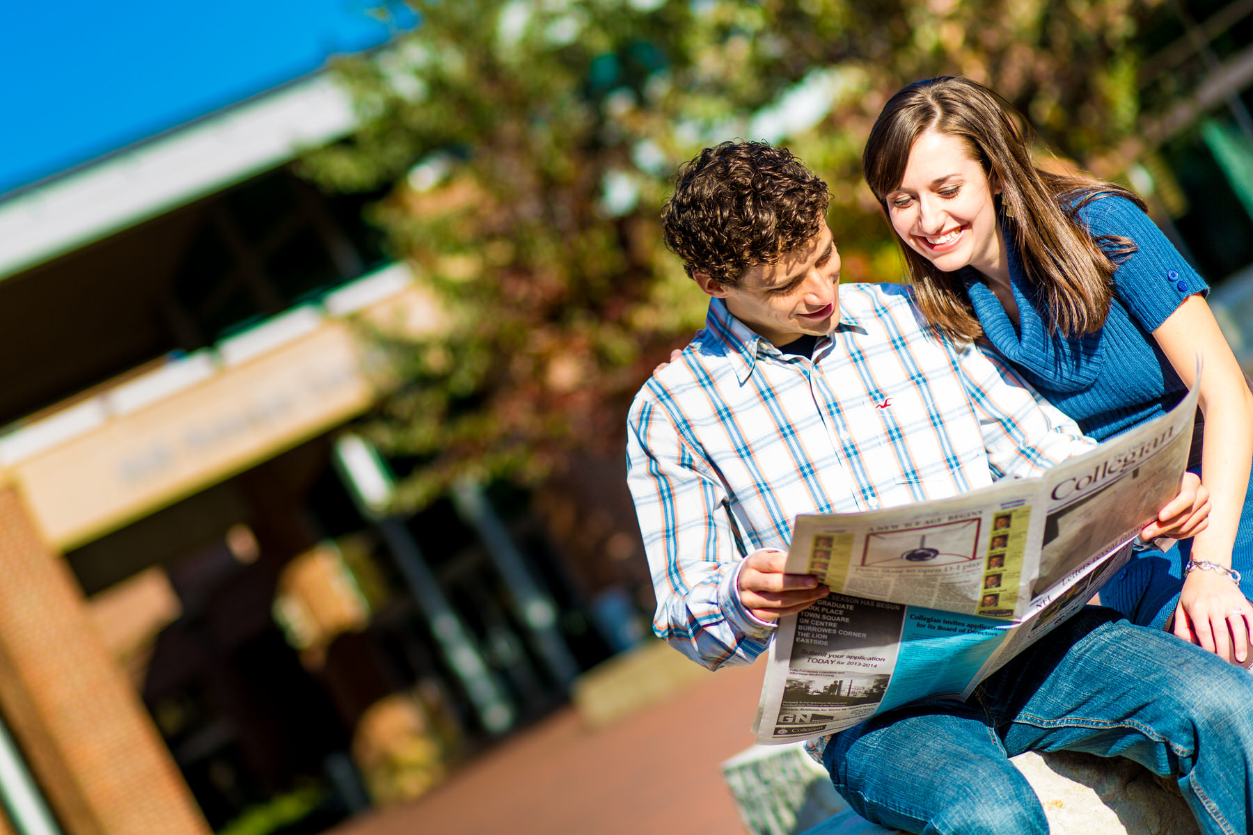 couple reading the Penn State newspaper during state college engagement by Washington DC Wedding Photographer Adam Mason