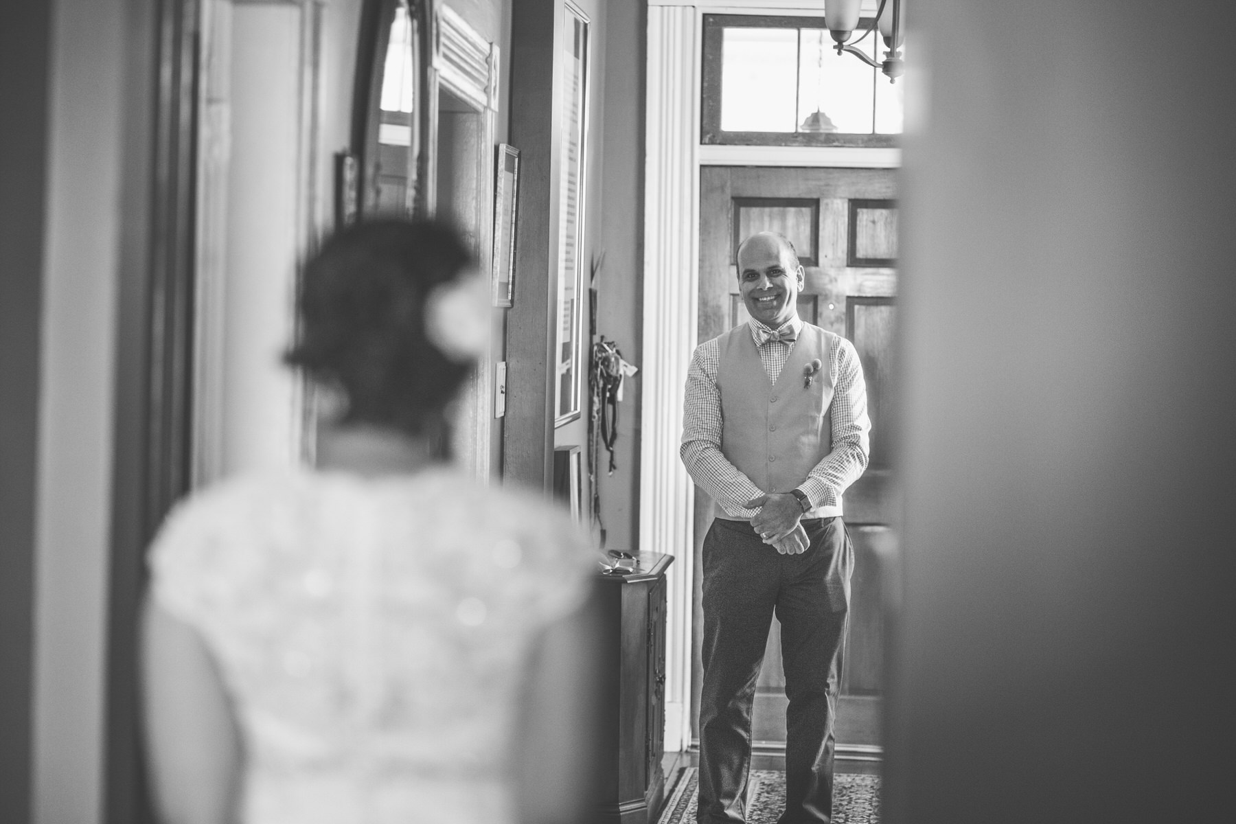 father waiting at bottom of stairs for bride, his daughter for father daughter first look by Washington DC Wedding Photographer Adam Mason