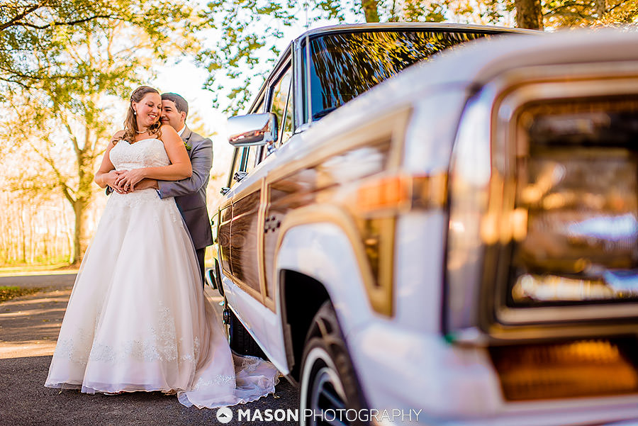 bride and groom with classic car on wedding day