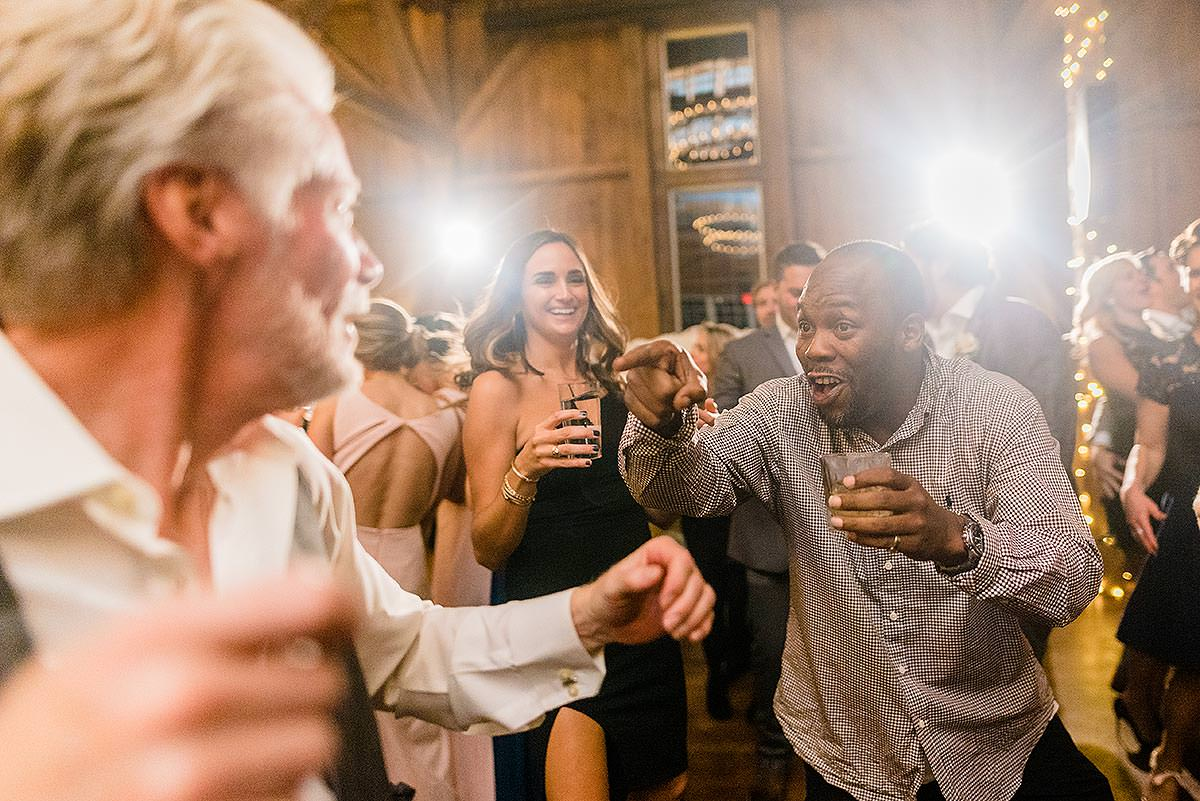 one wedding guest laughing with another as they dance at wyndridge farm wedding