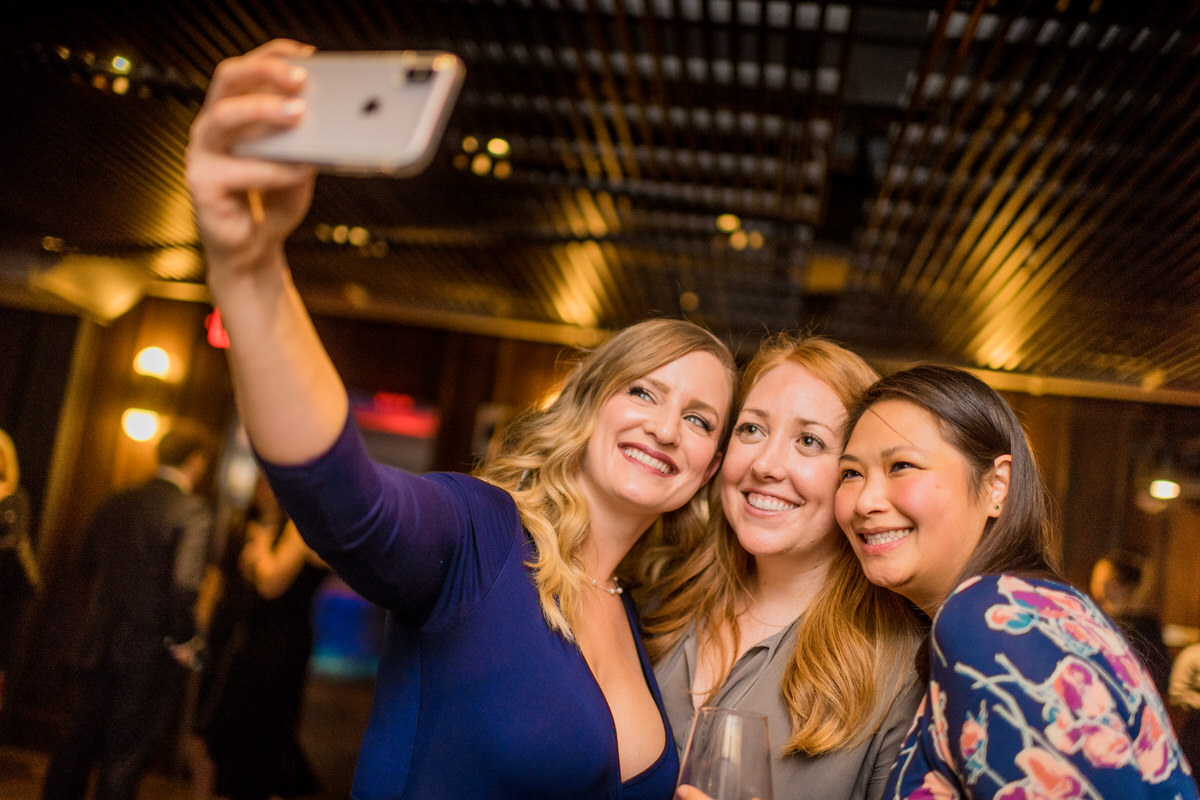 wedding guests taking selfie during district winery mezzanine cocktail hour