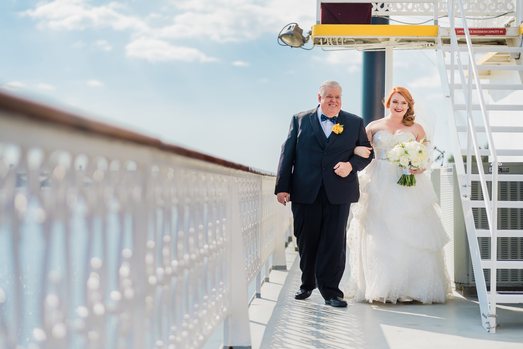 The bride makes her way down the aisle on the Potomac Riverboat Company's Cherry Blossom riverboat by Washington DC Wedding Photographer Adam Mason