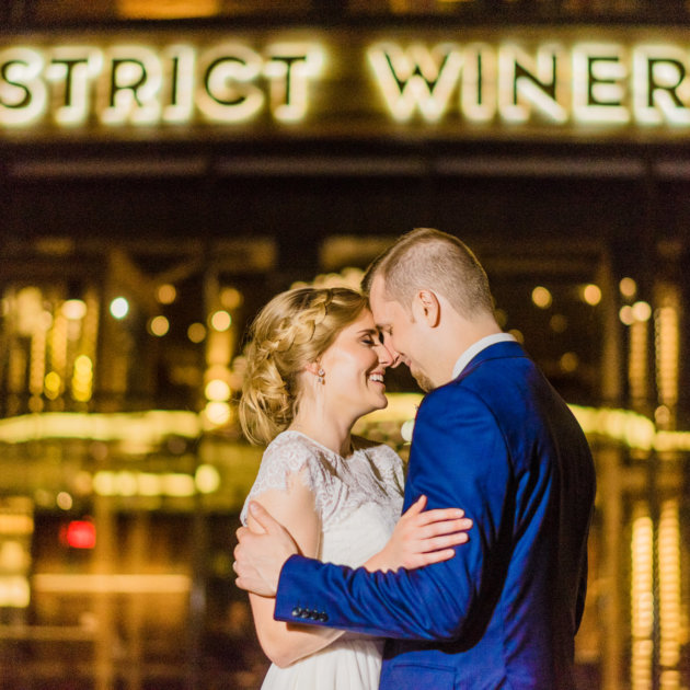 bride and groom embrace in front of district winery exterior during district winery wedding by Washington DC Wedding Photographer Adam Mason