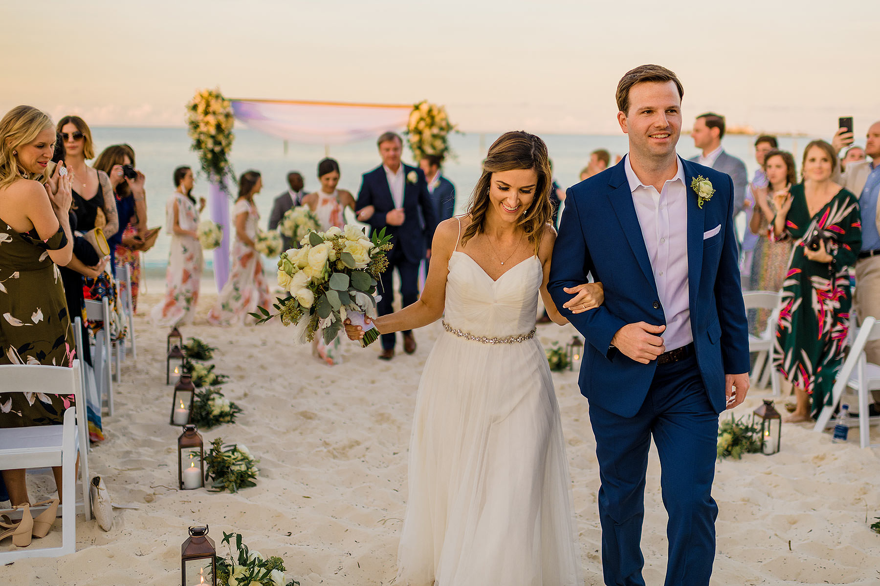 bride and groom laugh as they walk in the sand down the aisle after their Bahamanaian wedding at grand hyatt baha mar by bahamas wedding photographer adam mason