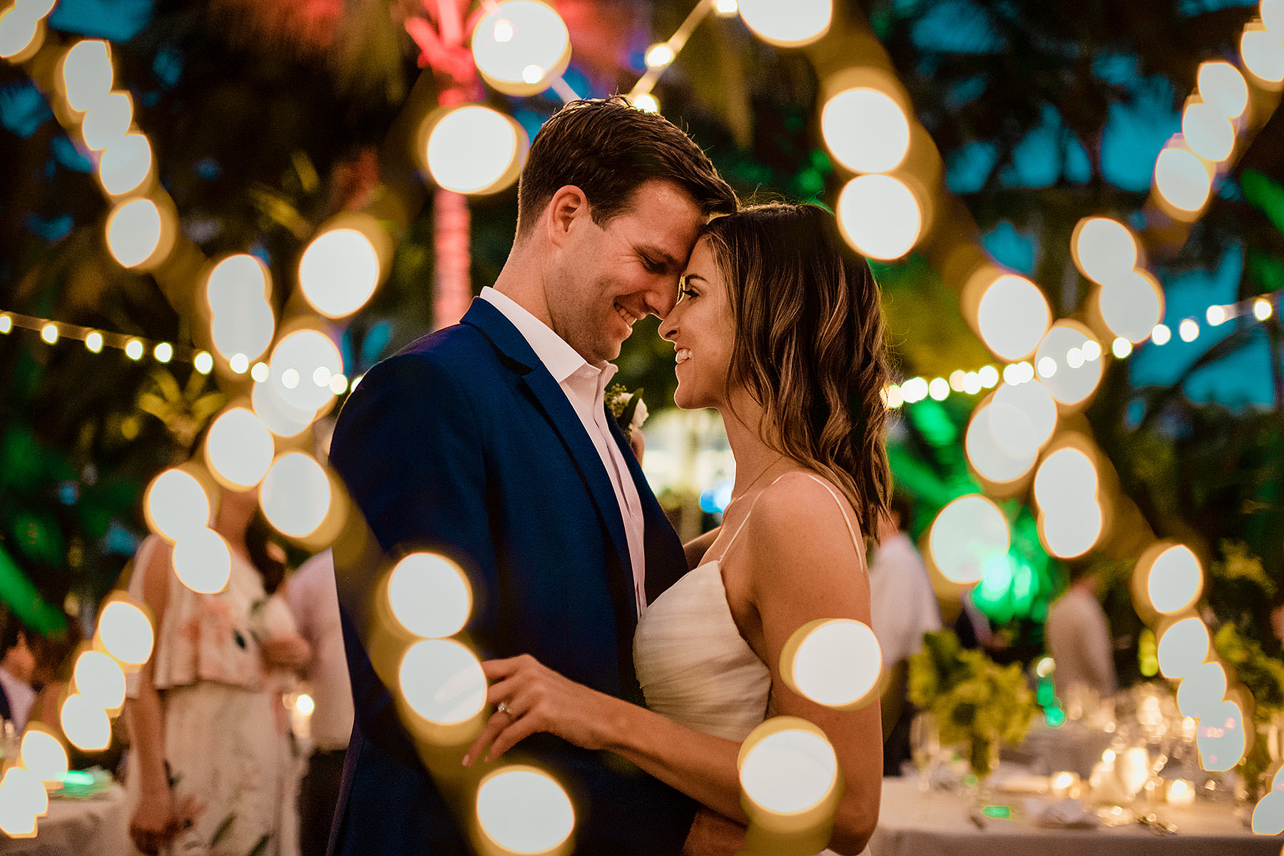 creative double exposure wedding photo of couple in the bahamas by outdoor reception bride and groom dance bahamas wedding by wedding guests dancing during outdoor wedding reception grand hyatt baha mar by bahamas wedding photographer adam mason