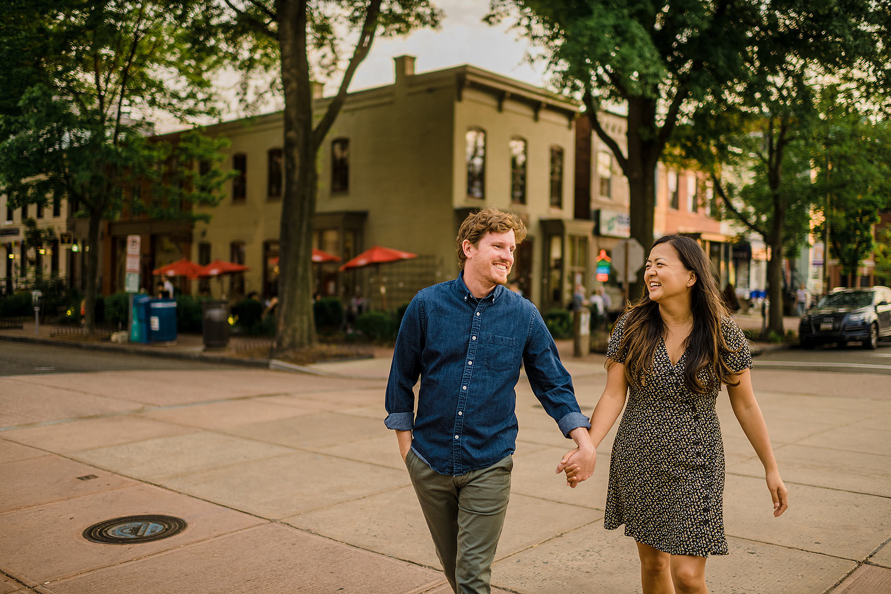 couple walking during romantic sunset through eastern market intersection during capitol hill engagement session by Washington DC Wedding Photographer Adam Mason