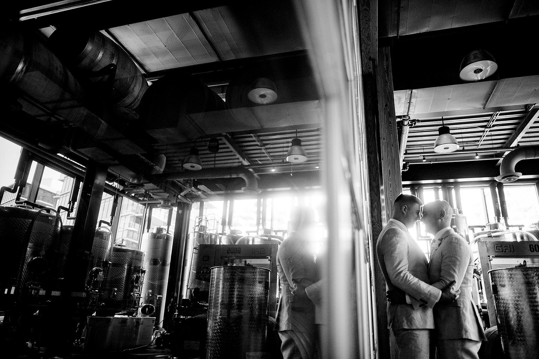 two grooms in the barrel winery room at district winery wedding by Washington DC Wedding Photographer Adam Mason