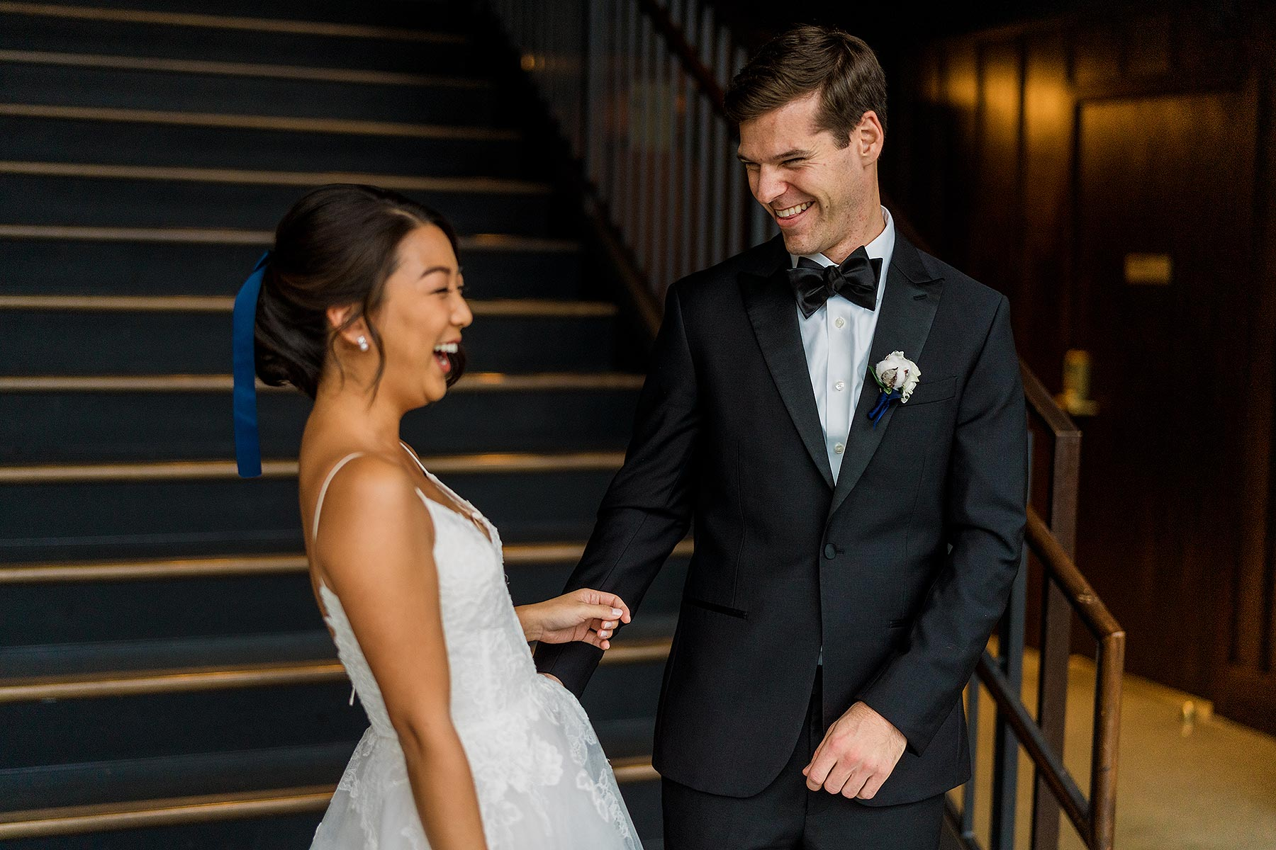 groom smiling at bride during first look on the stairs at district winery wedding by Washington DC Wedding Photographer Adam Mason