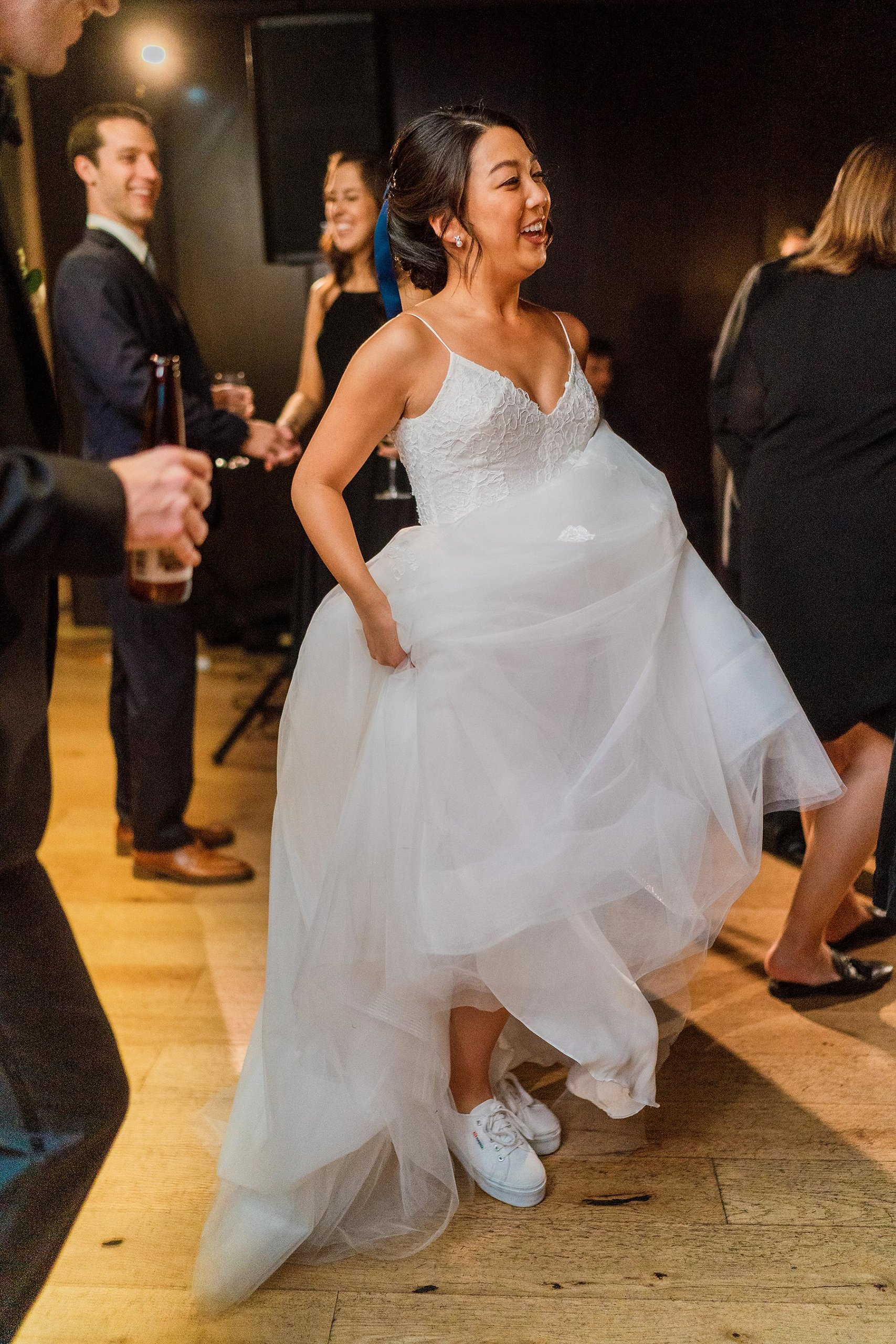 bride wearing keds or toms shoes and smiling at district winery wedding by Washington DC Wedding Photographer Adam Mason