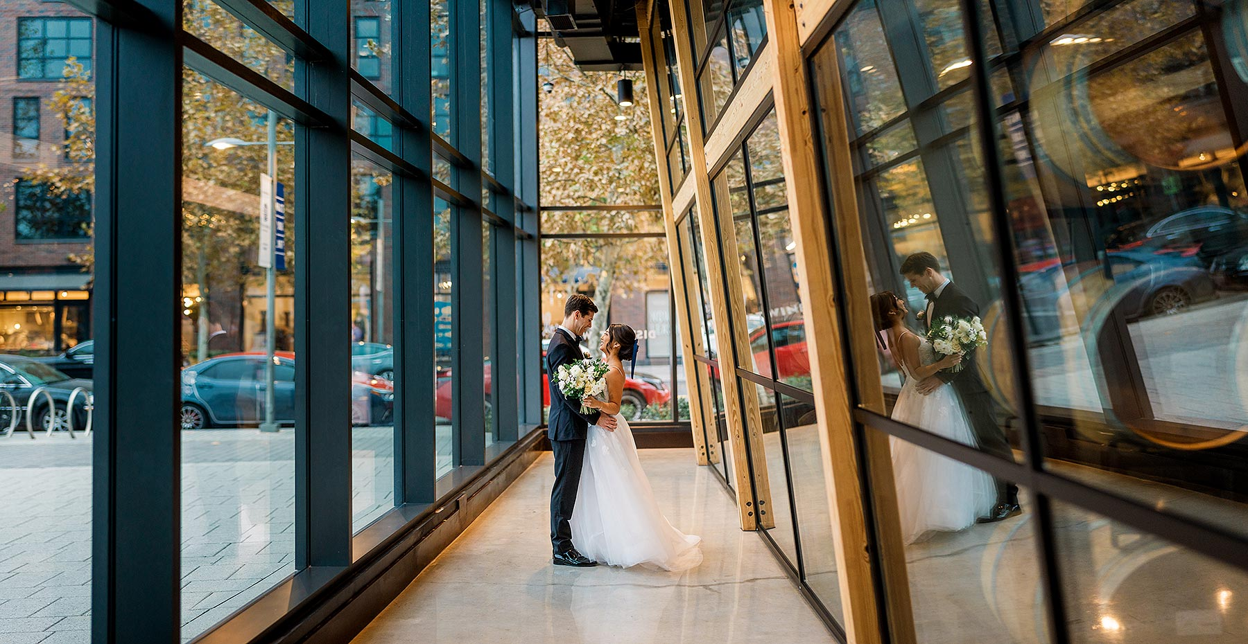 creative wedding photo in glass window hallway at district winery wedding by Washington DC Wedding Photographer Adam Mason