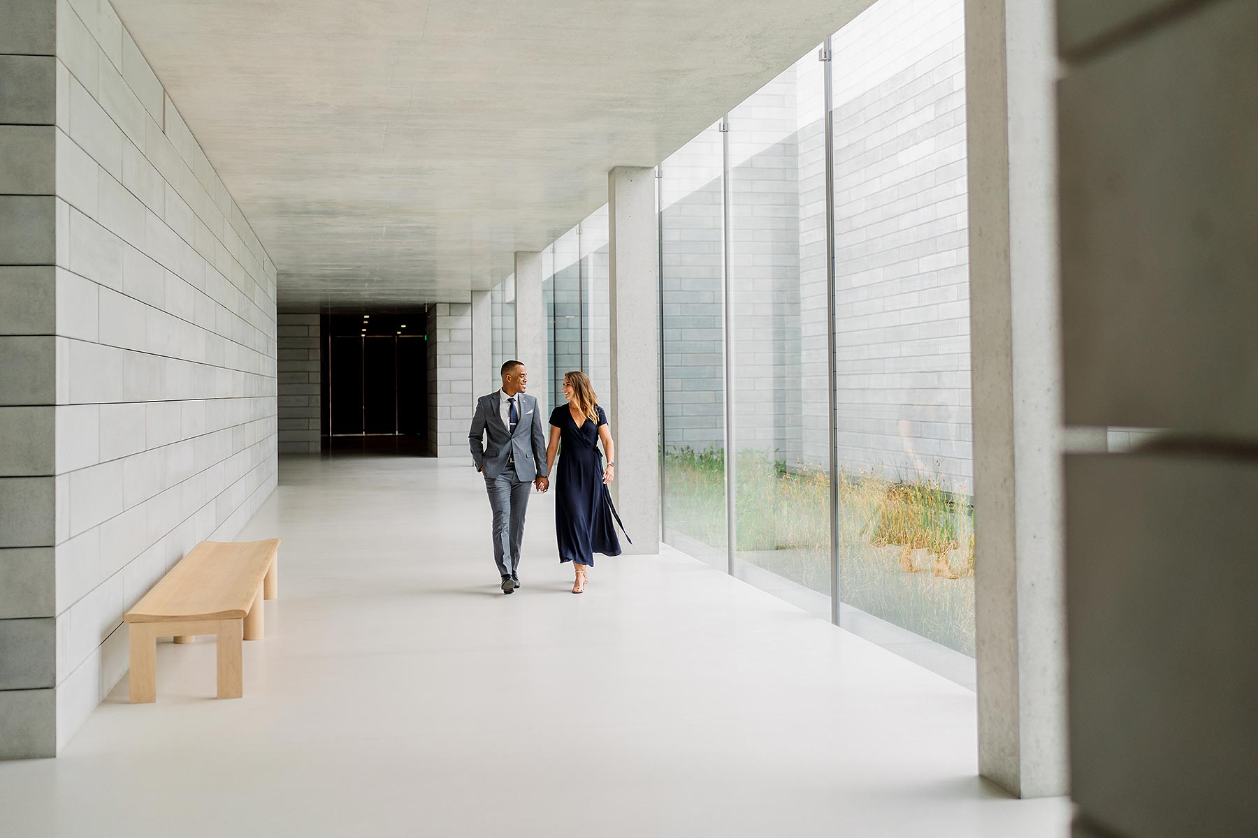 interracial couple in formal clothes walking inside during glenstone engagement session by Washington DC Wedding Photographer Adam Mason