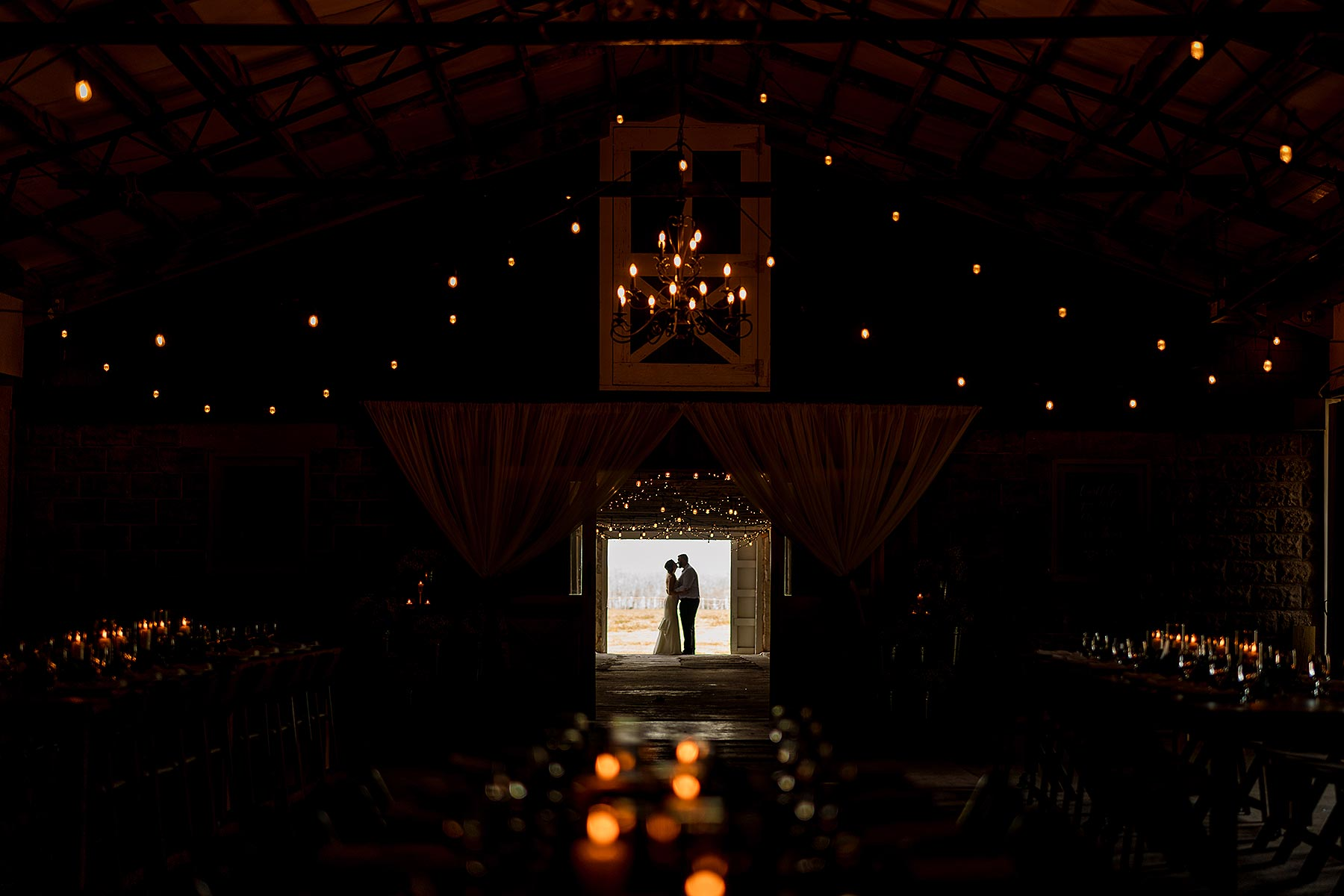 creative silhouette of couple in farmhouse with twinkly lights at hopkins heartland by Washington DC Wedding Photographer Adam Mason